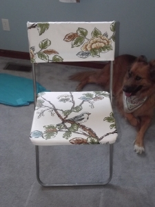 Decoupaged folding chair with slip cover.